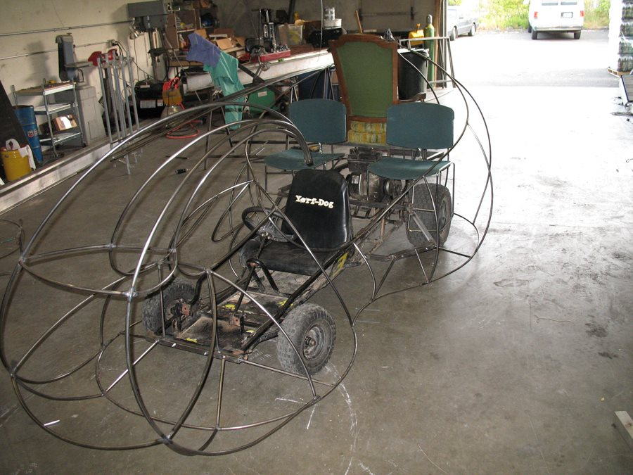 A stretched go-kart chassis with steel wire frame.